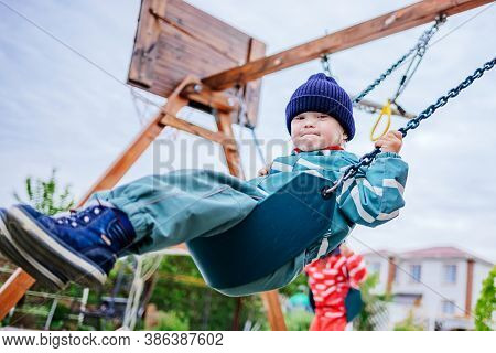 A Boy With Down Syndrome Plays On The Playground, He Is Swinging On A Swing. Genetic Disease In A Ch