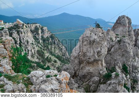 Hanging Suspension Bridge Over Abyss In Steep Rocks Ai-petri, Crimea. Cliff Against The Backdrop Of