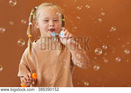 Waist Up Portrait Of Cute Girl With Down Syndrome Blowing Bubbles While Posing Against Brown Backgro