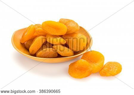 Preserved fruit. Dried sulfurized apricots in and out of wooden bowl isolated on white background.