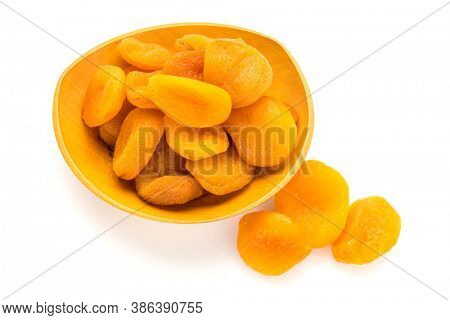 Preserved fruit. Dried sulfurized apricots in and out of wooden bowl isolated on white background. High angle view.