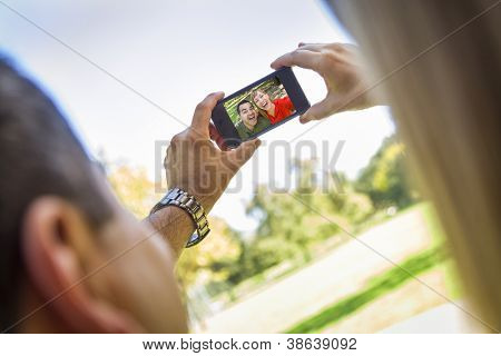 Happy Mixed Race Couple Taking Self Portrait at the Park.