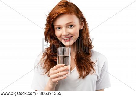 Positive Ginger-haired Young Woman Holding Glass Of Water Smiling To Camera Standing Over White Stud