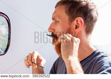 Man Cutting His Own Beard And Mustache With Scissors And Comb. Caucasian Red Bearded Male Trimming H