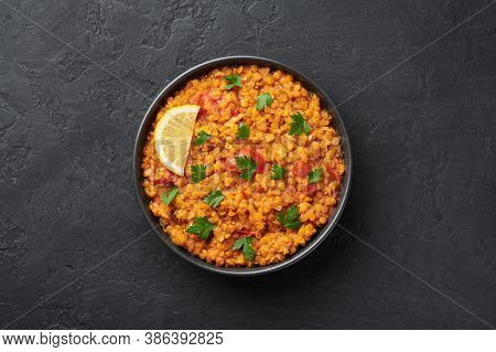 Red Lentils Dal In Black Bowl On Dark Slate Table Top. Lentils Tomato Dhal Is Indian Cuisine Dish Wi