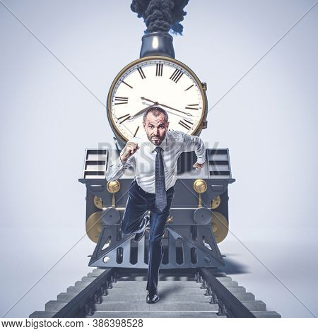 man running on the tracks and running away from a train with a big clock. concept of time, urgency.