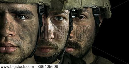 Close Up Portrait Of Young Male Soldiers. Men In Military Uniform On The War On Black Background. De