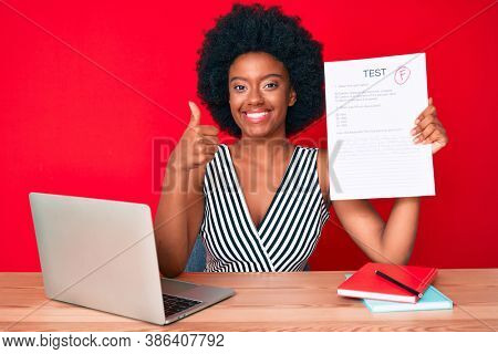 Young african american woman showing a failed exam smiling happy and positive, thumb up doing excellent and approval sign