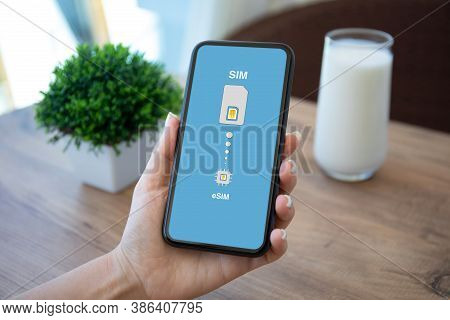 Female Hand Holding Phone With Sim Card Replacement On Esim In Room House