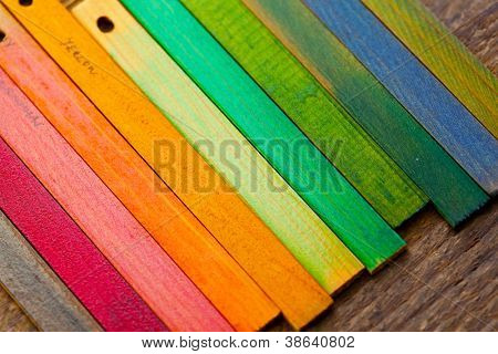 Colorful wood stain color test samples, on rough wood.