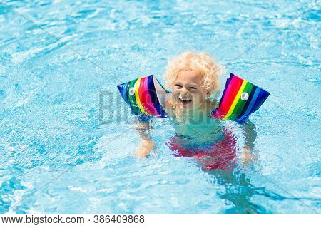 Child In Swimming Pool Wearing Colorful Inflatable Armbands. Kids Learn To Swim With Float Aid.