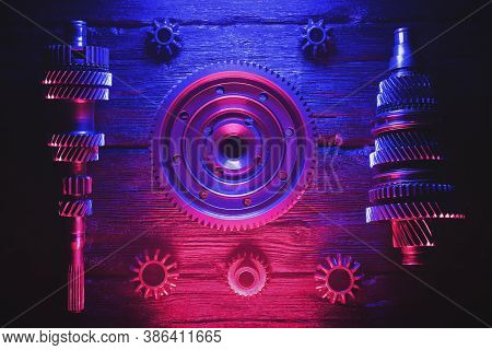 Primary And Secondary Shaft Of The Car Gearbox On Black Background In The Neon Lights. Car Service B