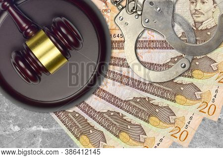 20 Dominican Peso Bills And Judge Hammer With Police Handcuffs On Court Desk. Concept Of Judicial Tr