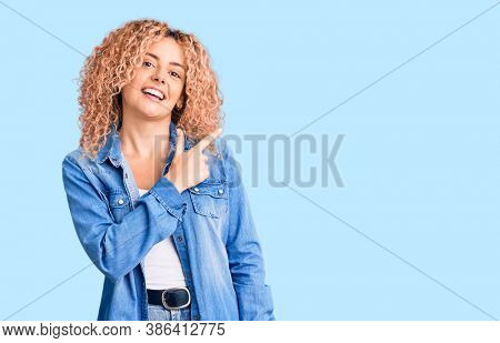 Young blonde woman with curly hair wearing casual denim jacket cheerful with a smile of face pointing with hand and finger up to the side with happy and natural expression on face