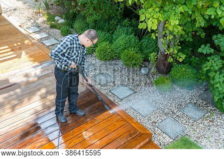 Power Washing - Man Cleaning Terrace With A Power Washer - High Water Pressure Cleaner On Wooden Ter