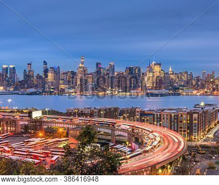 New York, New York, USA cityscape and highways from across the Hudson River at dusk.