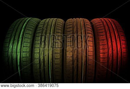 Studio Shot Of A Set Of Summer Car Tires Isolted On Black Background In Green And Red Tones. Car Tyr