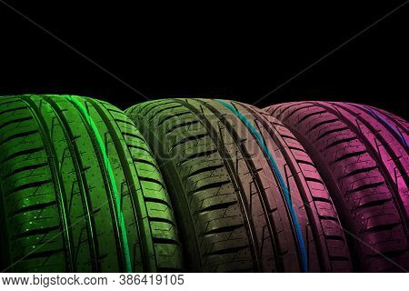 Studio Shot Of A Set Of Summer Car Tires In Green And Pink Tones. Tire Stack Background. Car Tyre Pr
