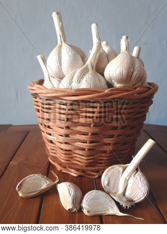 Closeup Garlic Are In The Wicker Basket On The Wooden Table.properties To Help Reduce Cholesterol.