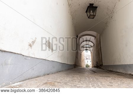 Narrow Inner Paved Stone Urban Street Road Passage In Old European City. Vintage Dark Alley With Lam