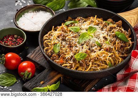 Pasta Bolognese In The Skillet At Black Table. Traditional Italian Food.
