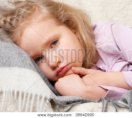 Illness child. Little girl wrapped in a blanket