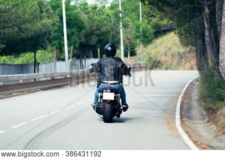 Rear View Of A Biker With Helmet And Leather Jacket Riding His Motorcycle On The Road, Concept Of Fr