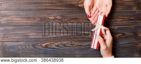Top View Of Holding A Gift In Female And Male Hands On Wooden Background. Woman And Man Give And Rec