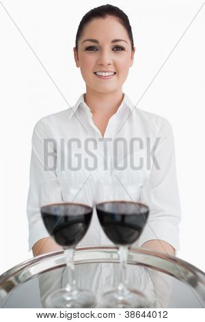 Waitress holding silver tray with glasses of red wine