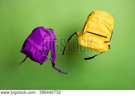 Two School Back Packs Modern Style Sacks Thrown Up Air On Green Color Background Season Low Prices S