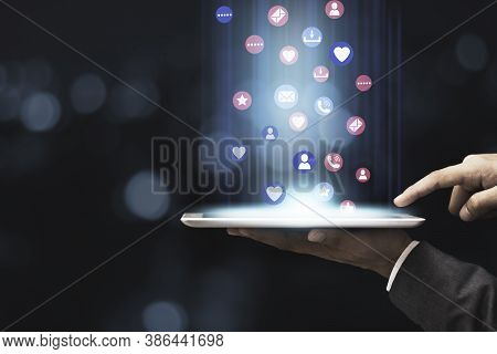 Businessman Holding Tablet With Glowing Blue Light With Social Media Icons On Blue Bokeh Background.