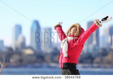 City winter woman happy standing excited and elated with arms raised in joy. Beautiful young woman and Montreal City skyline, Quebec, Canada.