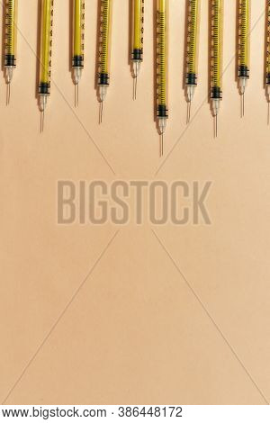 Top View Of Medical Syringes For Injections Lying Isolated Over Light Background. Injection Medicine