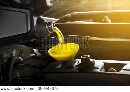 Mechanic Pouring Engine Oil To Car Engine In Garage Shop