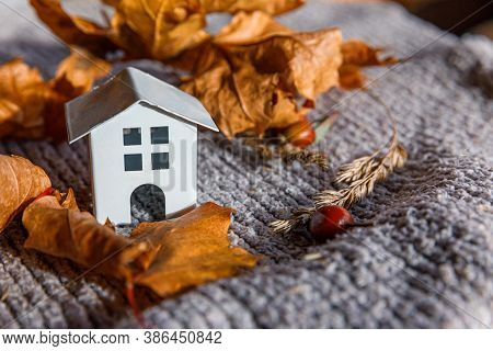 Autumnal Background. Toy House And Dried Orange Fall Maple Leaves On Grey Knitted Sweater. Thanksgiv