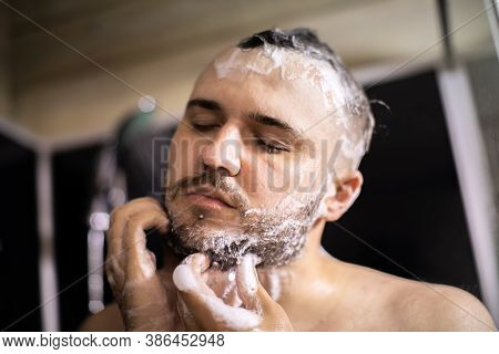Young Bearded Naked Brunette Man Washes His Beard And Head With Shampoo Foam. Advertising For Mens H