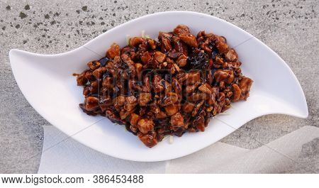 Fried chicken meat with soy sauce and walnuts