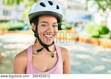 Young beautiful hispanic cyclist woman smiling happy wearing bike helmet at the town