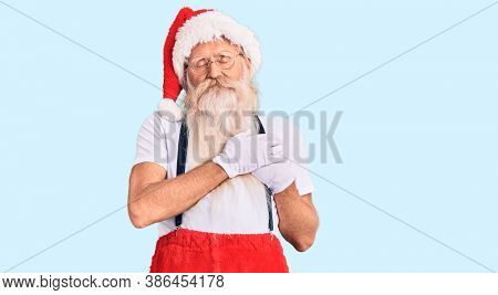 Old senior man with grey hair and long beard wearing santa claus costume with suspenders smiling with hands on chest with closed eyes and grateful gesture on face. health concept.