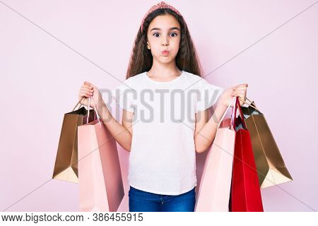 Cute hispanic girl holding shopping bags puffing cheeks with funny face. mouth inflated with air, catching air.