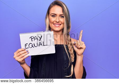 Beautiful blonde woman asking for equality economy holding paper with pay equal message smiling with an idea or question pointing finger with happy face, number one