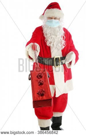 Coronavirus Santa Claus. Santa wears a paper face mask and holds a Christmas gift at a distance with his holiday extension arm. Covid-19 has caused a world wide pandemic.