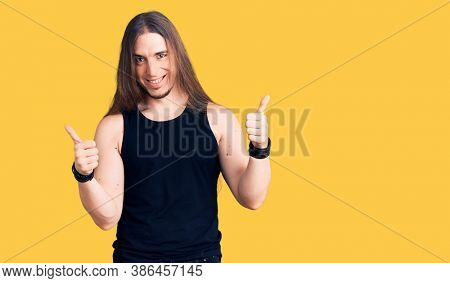 Young adult man with long hair wearing goth style with black clothes success sign doing positive gesture with hand, thumbs up smiling and happy. cheerful expression and winner gesture.