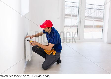 Young Handsome Professional Plumber Worker Installing Heating Radiator In An Empty Room Of A Newly B