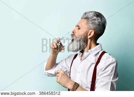 Gray-haired, Bearded Elderly Man In A White Shirt And Brown Suspenders. He Drinks Clear Water From C