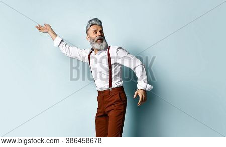 Gray-haired Bearded Man In A White Shirt, Brown Pants And Suspenders. He Tries To Run Away, Looks Ar
