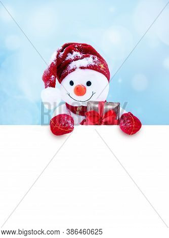 Little Snowman In Cap And Scarf On Snow In The Winter. Festive Background With A Funny Snowman. Chri
