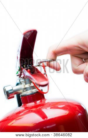 Hand pulling safety pin from red fire extinguisher