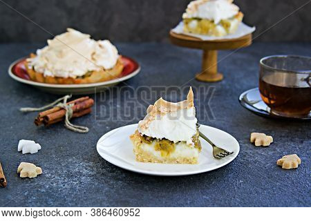 Mini Tarts With Custard, Gooseberries And Meringue On A White Plate On A Dark Concrete Background. D