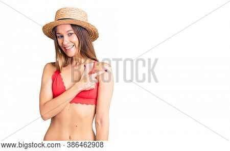 Beautiful brunette young woman wearing bikini cheerful with a smile of face pointing with hand and finger up to the side with happy and natural expression on face